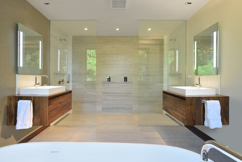 The glass door, large scale tiles and floating vanities make for a smooth and modern bathroom. The curbless shower is perfect to complete this design.
