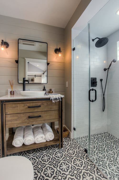 The patterned flooring tile looks great carried through the wet area. The oil rubbed bronze finishes mix well with the vintage style vanity.